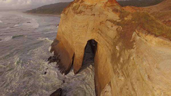 Aerial shot of hidden cave along Cape Kiwanda on the Oregon coast. Rights-managed stock video