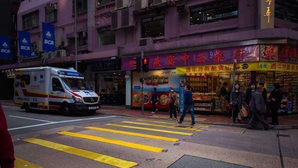 Timelapse pan shot of busy Hong Kong street with people and cars during the day. Rights-managed stock video