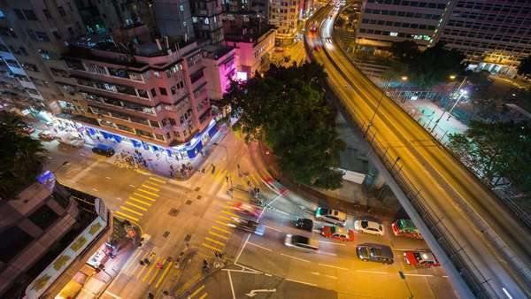 Timelapse static shot of busy Hong Kong street and freeway, birds eye view at night. Rights-managed stock video