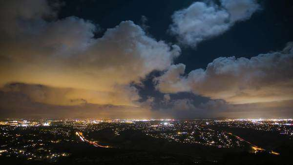Timelapse static shot of San Diego mountain view at night with clouds. Rights-managed stock video