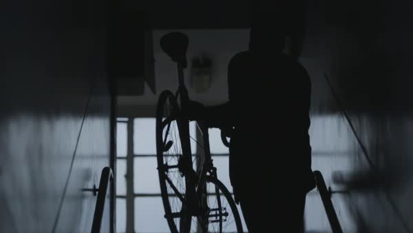 Slow motion shot of a man carrying his bicycle up a staircase Royalty-free stock video