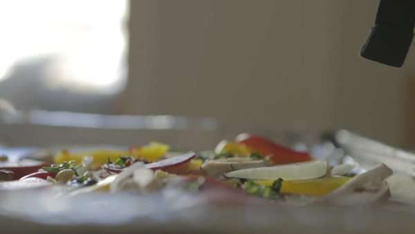 Shot of hands laying out toppings over a pizza Royalty-free stock video