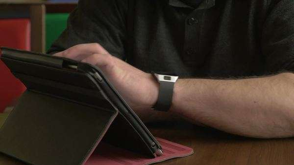 Businessman working on a smart watch and tablet pc in a coffee shop Royalty-free stock video