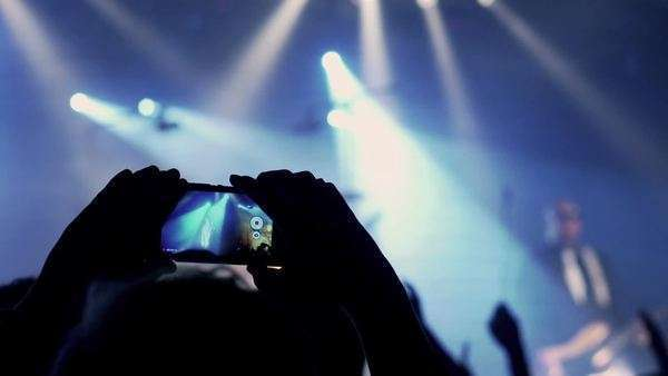 Man recording concert on cellphone and crowd having fun, steadicam shot Royalty-free stock video