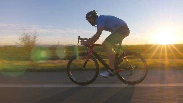 Healthy man riding bicycle outdoors at sunset tracking shot from camera car Royalty-free stock video