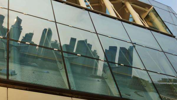 Singapore,singapore,15/08/2015:modern city skyline cityscape of singapore reflected on mirror  glass surface pan shot Royalty-free stock video