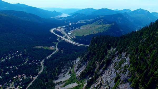 Sideways moving shot of a rocky, green alpine mountain valley in summertime, revealing a highway, trees, paths and a wide beautiful valley mountain mountains Royalty-free stock video
