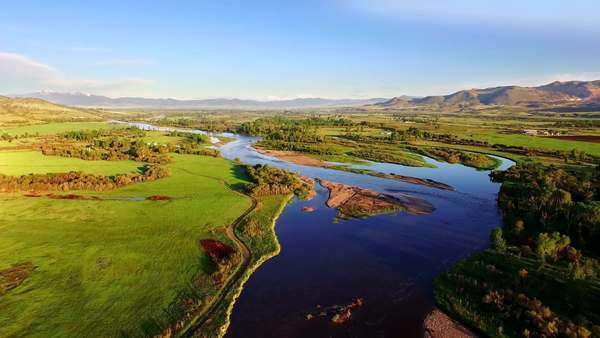 Breathtaking aerial of a beautiful river in a farming valley on a gorgeous, colorful, sunny morning with hills and snow top mountains in the background Royalty-free stock video