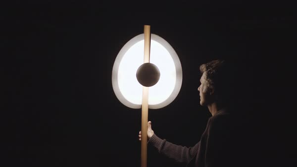 Static shot of a man examining and turning off a, artistic floor lamp that he created Royalty-free stock video