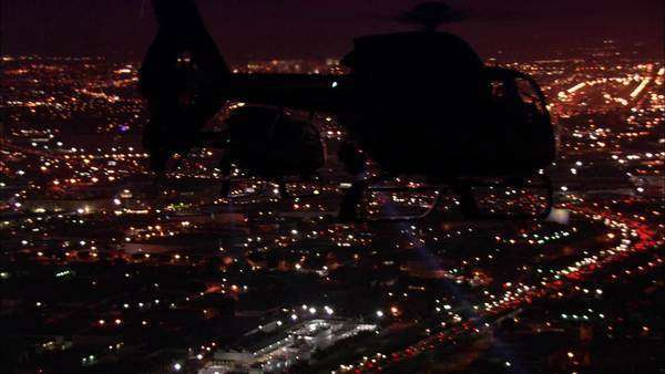 Wide shot of helicopters flying above a city at night Royalty-free stock video