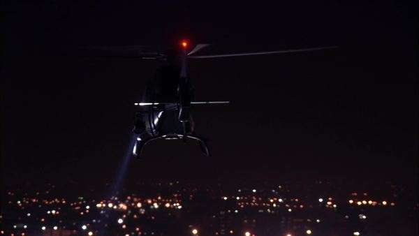 Wide shot of a helicopter flying above a city at night Royalty-free stock video