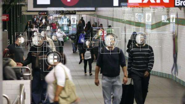 A computer scans a crowded subway tunnel, using facial recognition to show each person's personal data in a floating display that follows the individual. Each display has a photo of the person, a unique fingerprint, and basic information like name, race, age, etc. The small blocks of text mostly have scrolling excerpts of code. Royalty-free stock video