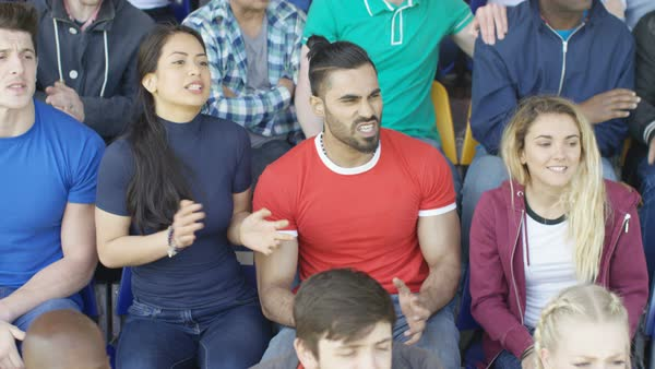 Sports fan sitting with supporters of the other team shows disappointment Royalty-free stock video