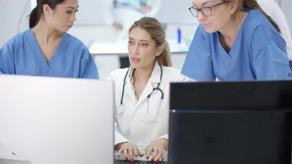 Female medical team in modern hospital looking at computer and having a meeting Royalty-free stock video