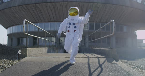 Funny astronaut doing a dance as he walks away from mission control building. Royalty-free stock video