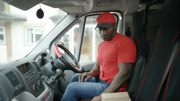 Delivery driver unloading boxes from back of van, as seen from ...