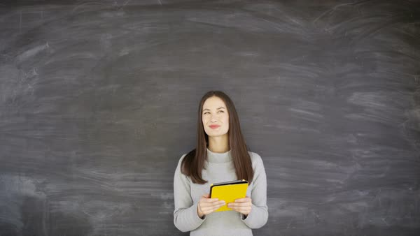 Cheerful pensive woman with tablet computer on blank chalkboard background Royalty-free stock video
