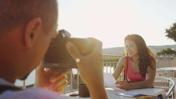 Photographer taking pictures of attractive woman sitting near the sea Royalty-free stock video
