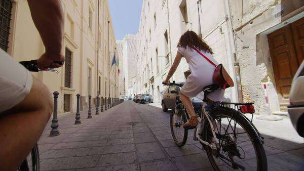 Attractive woman cycling through the city in summertime Royalty-free stock video