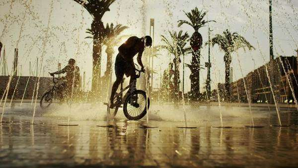 Young boys on bikes cooling off in fountain in the city in summertime Royalty-free stock video