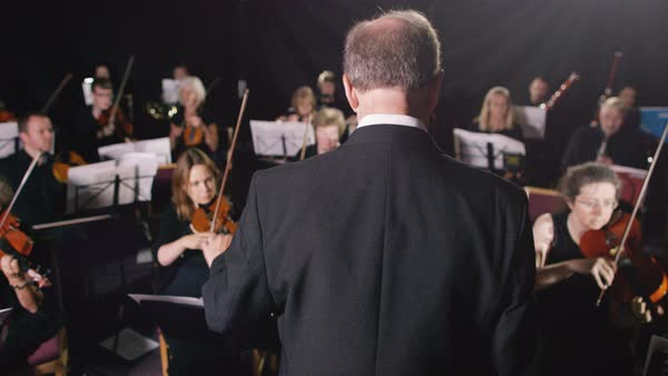 Symphony orchestra during a performance with close up on violinist Royalty-free stock video