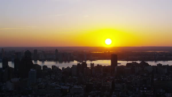 Aerial shot of sunset over New York City skyline. Silhouette cityscape skyscrapers and iconic landmarks. Sunrise golden glow over office blocks, stores and Manhattan apartments. Royalty-free stock video