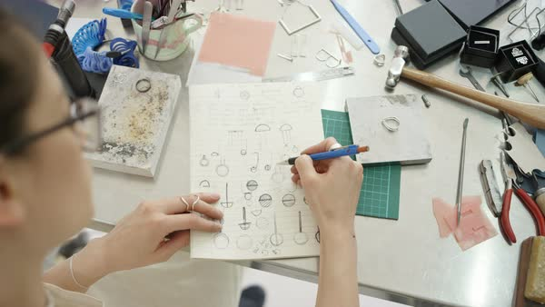 Overhead view looking down jewelry designer in studio sketching out designs.  Royalty-free stock video