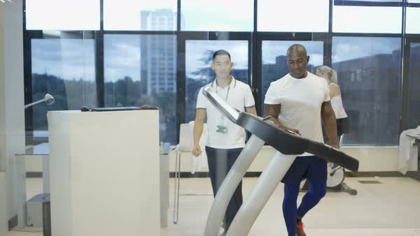 Man with personal trainer using treadmill in modern gym Royalty-free stock video