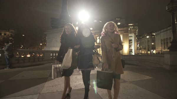 Happy female friends with shopping bags walking through the city at night. Royalty-free stock video