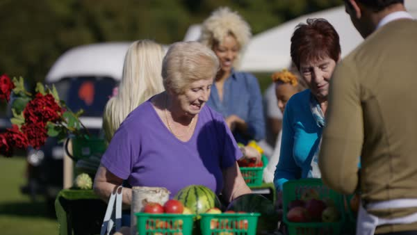 Friendly stall holders selling fresh produce to customers at the farmers market. Royalty-free stock video
