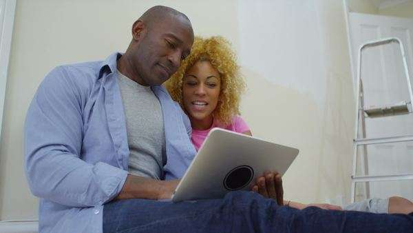 Happy attractive couple with computer tablet relax and take a break from painting in new home. Royalty-free stock video
