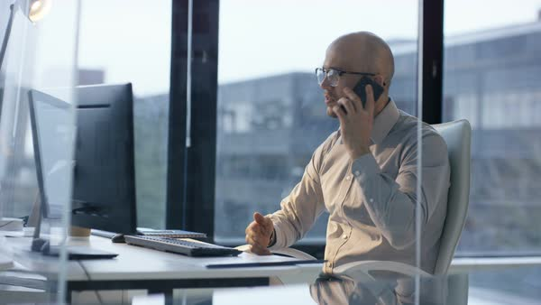 Businessman  in glass modern office with large windows, working at his desk and making a phone call.  Royalty-free stock video