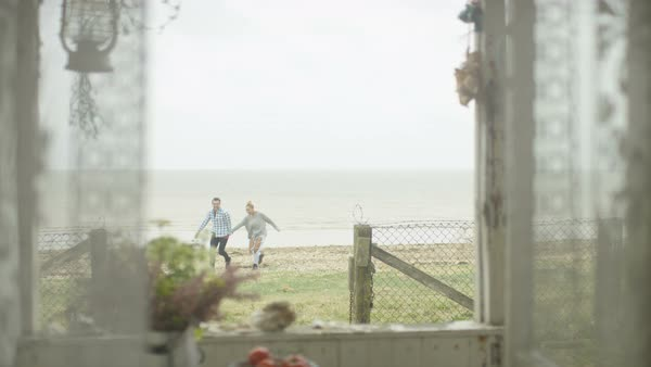 Romantic young couple embracing at beach house and looking out at the view. Royalty-free stock video
