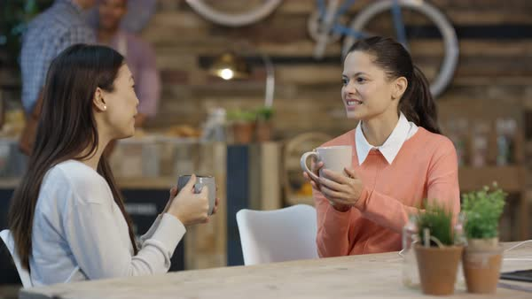Happy female friends chatting over coffee in trendy city cafe Royalty-free stock video