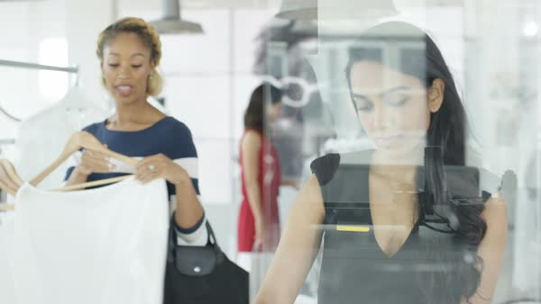 Female customers shopping and clerk giving assistance in fashionable boutique clothing store. Royalty-free stock video