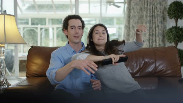 Couple fighting over the remote control in front of TV. Royalty-free stock video