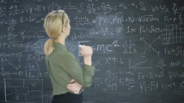 Portrait smiling academic woman in classroom studying math formulas on blackboard. Royalty-free stock video
