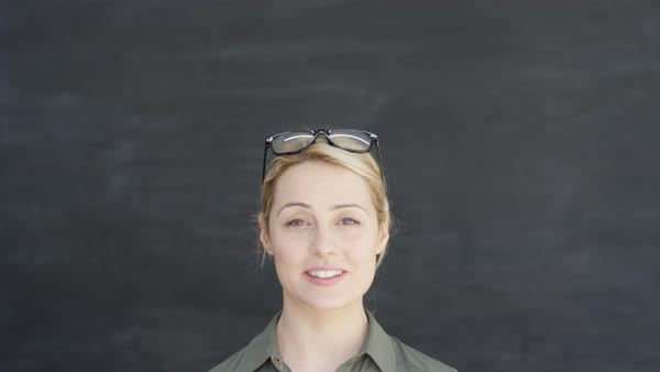 Portrait smiling woman on chalkboard background, camera panning downwards from blank copy space. Royalty-free stock video