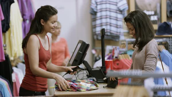 Customer in clothing store paying for a purchase with her credit card. Royalty-free stock video