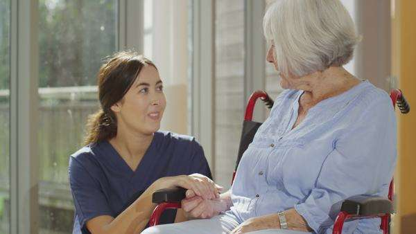 Caring nurse giving support to elderly female patient in a hospital or residential care home Royalty-free stock video