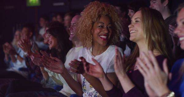 Young theatre audience clapping the performers on stage (focus on the audience only). Royalty-free stock video