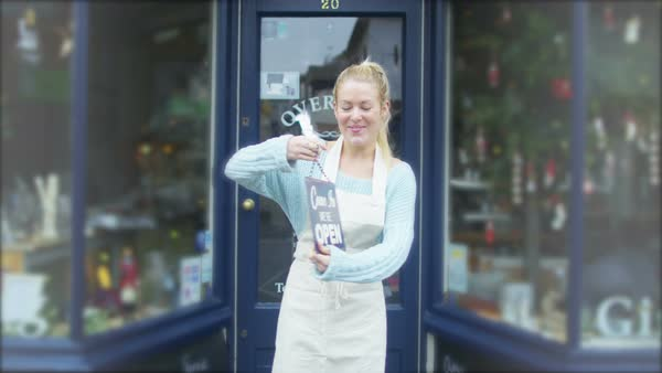 Happy female shopkeeper holds up a sign to show she is open for business. Royalty-free stock video
