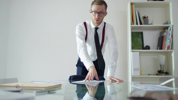 Young businessman pushing papers across desk in a confrontational manner, seen from 1st person perspective. Royalty-free stock video