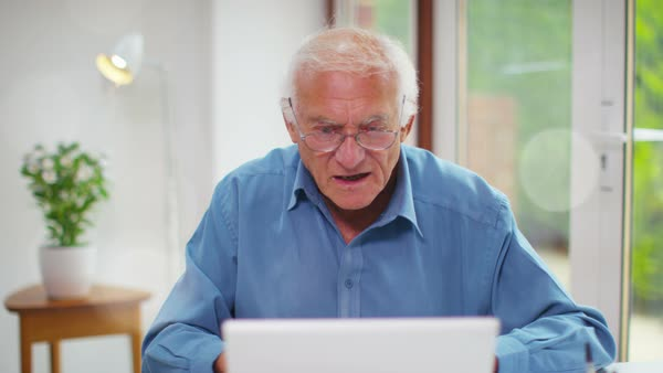 Happy senior man talking on video call on a laptop computer. Royalty-free stock video