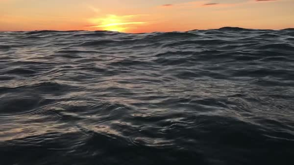 Slow motion shot of waves with sunset along horizon Royalty-free stock video