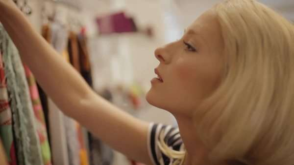 Medium close-up shot of a woman trying on scarf in a fashion store Royalty-free stock video
