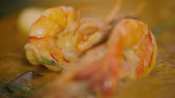 Prawns cooking in a sauce in a frying pan by a chef Royalty-free stock video
