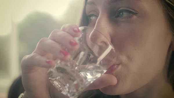 Close-up shot of woman drinking a glass of water in front of the window Royalty-free stock video