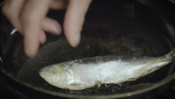Close-up shot of a person placing fish in a frying pan Royalty-free stock video