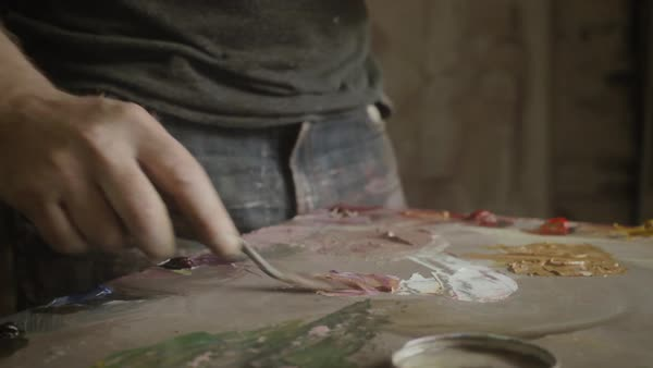 Hand-held shot of a man mixing colors with a painting knife Royalty-free stock video
